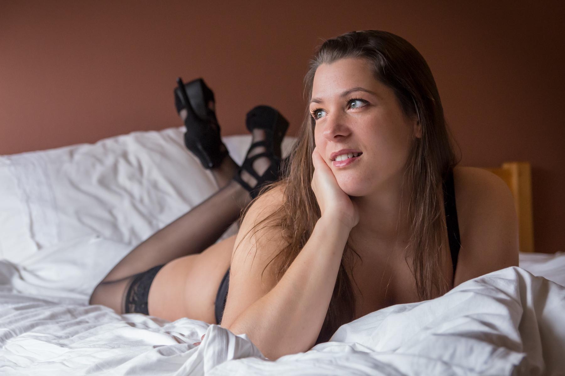 Boudoir fotoshoot liggend op het bed.